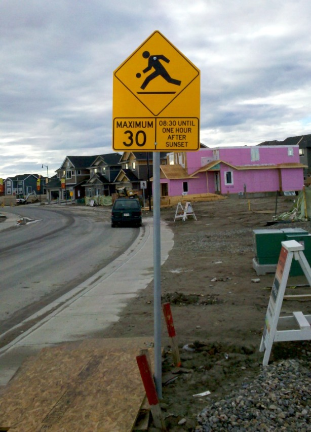 Please slow down: Construction workers by be bouncing a basketball on their break. It's generally uncommon for all street signs to be installed on streets that are still, for most part, a construction zone. This was taken in Sunset Ridge in Cochrane.