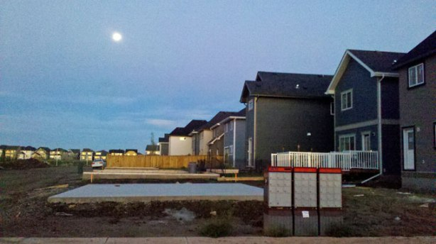 The moon sets in the southeast community of Mahogany on a row of lived-in houses still landing for their landscaping to be done and their garages built. At least Canada Post seems quick to keep up, though.